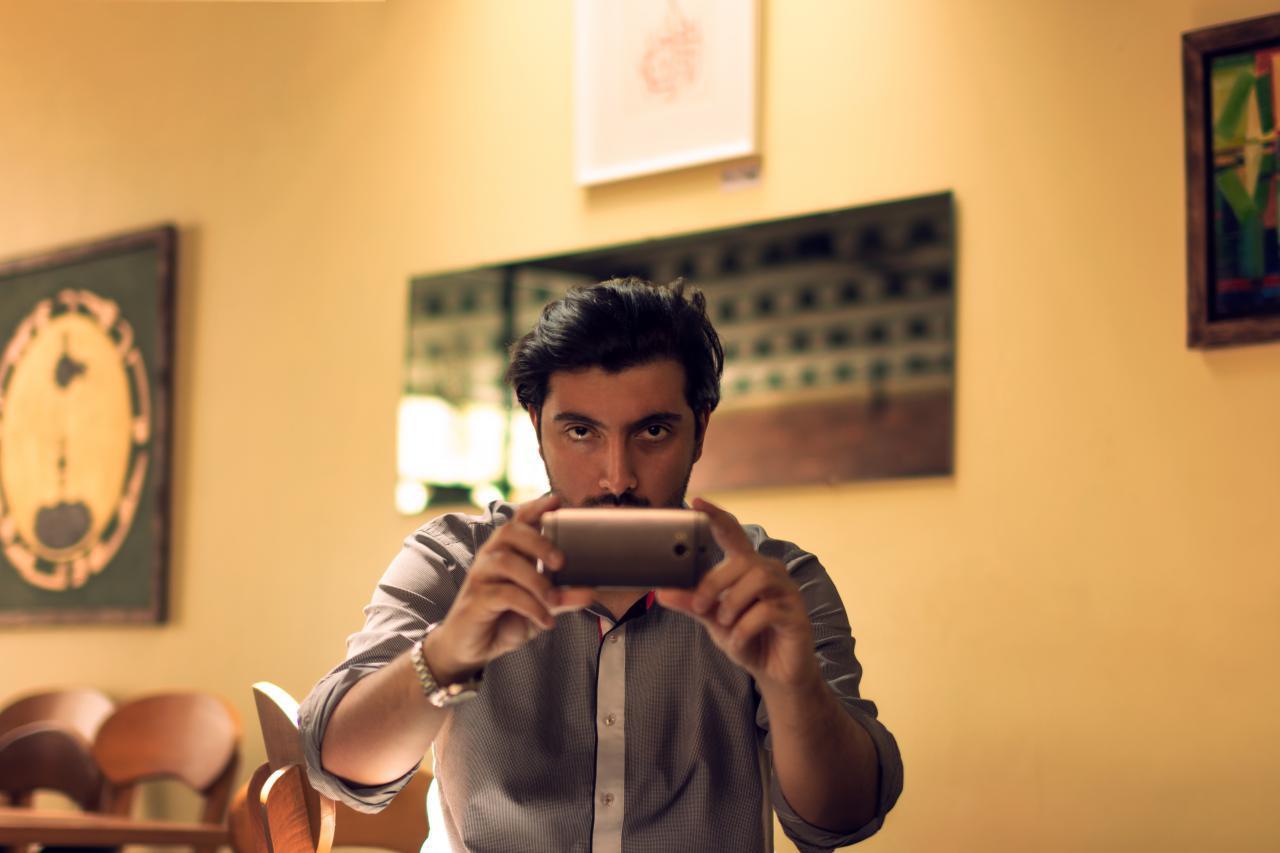 محمدرضا صادقی ملقب به رضاصاد در حال عکاسی با موبایل در کافه اربن سعادت آباد
