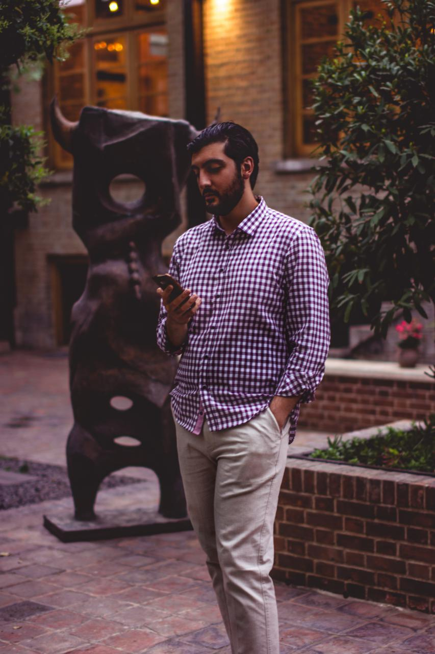محمدرضا صادقی یا رضاصاد در حال کار کردن به موبایل خود در کافه ری را