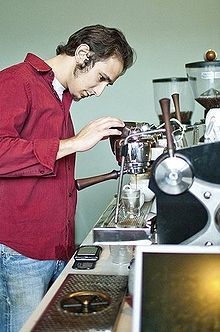 یک باریستا در حال کار با ماشین اسپرسو