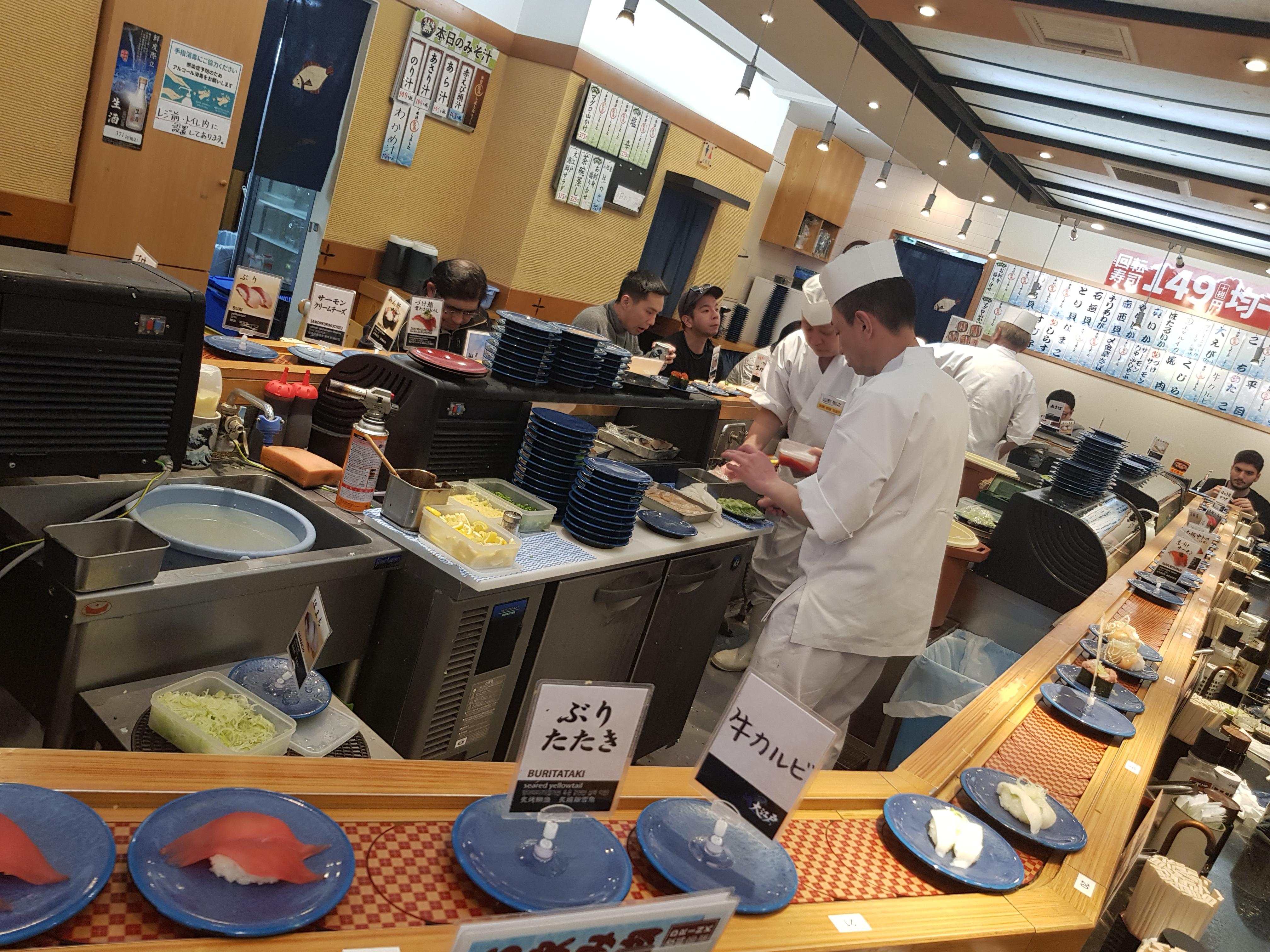 آشپزهای در حال درست کردن سوشی ها و قراردادن روی ریل مورد نظر