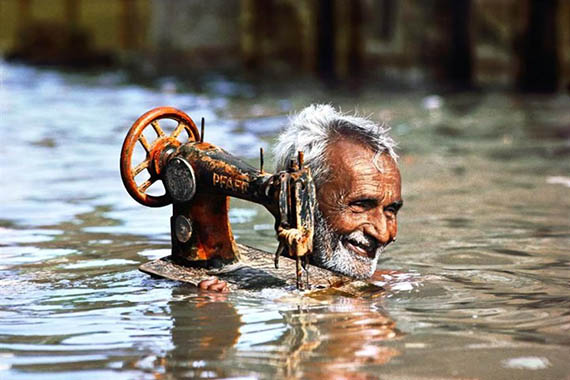 یک خیاط،چرخ خیاطی خود را از سیل نجات می دهد.پربندر،گجرات،سال1983